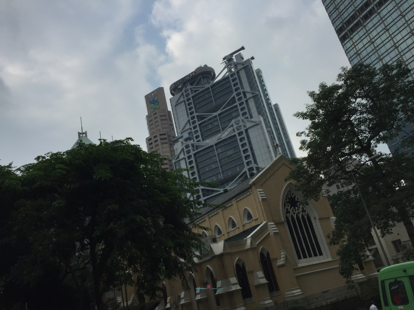 Looking at the back drop is the HSBC- Hong Kong Shanghai Bank.. walking past Garden Road in Central looking at St. Johns Cathedral..